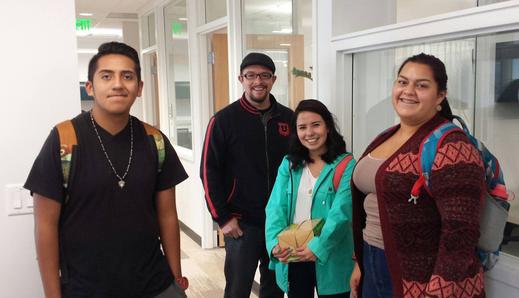 four students standing in hallway and smiling