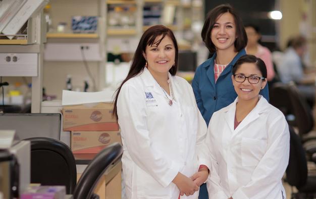 three women wearing lab coats in a lab setting