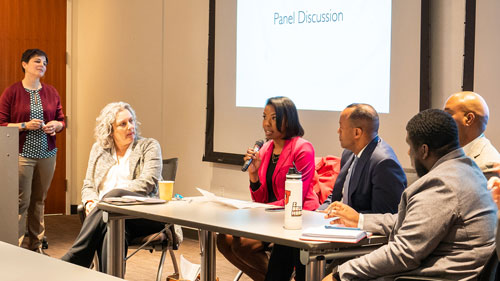 group of professionals sitting at a table with a projector screen behind them, one panelists is holding a microphone while the others look at her