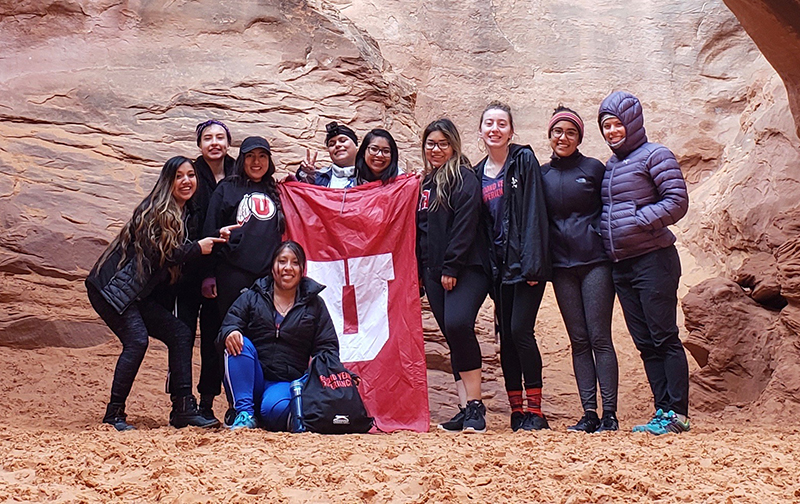 group of Second Year Experience participants holding a red and white Block U flag at Arches National Park