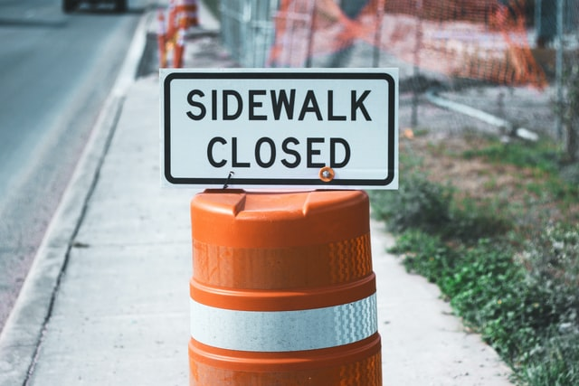 sidewalk blocked by construction barrier that reads: sidwalk closed