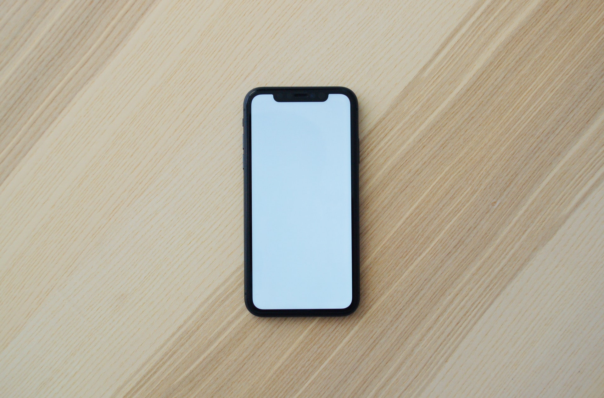 cellphone with blank white screen on a light wood tabletop