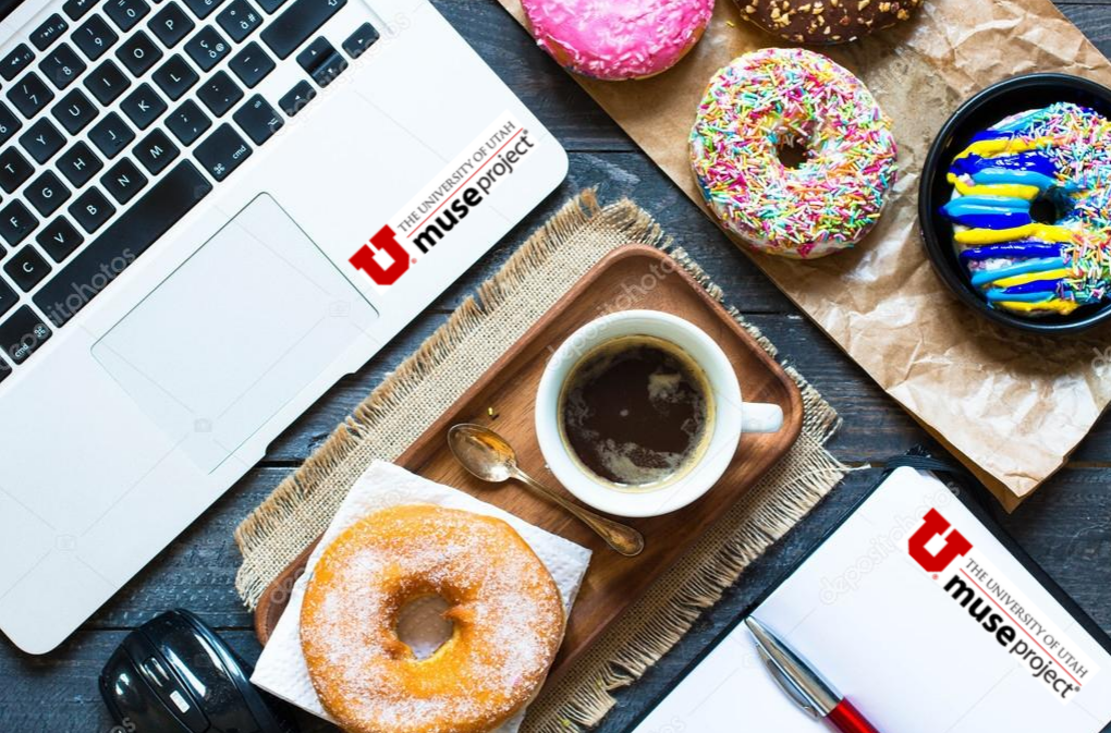 This is a photo of a table top with a laptop, notepad, cup of coffee, and and various types of donuts