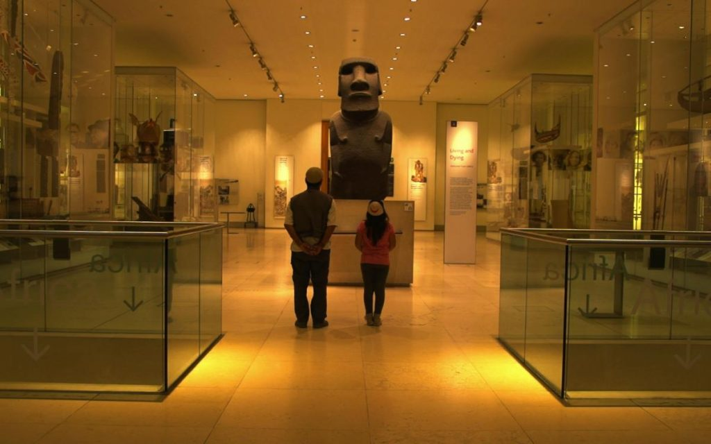 This is a photo of two people looking at a statue from a pacific islands culture.